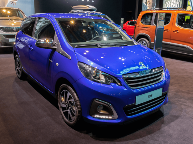 A blue Peugeot 108 in a street at night