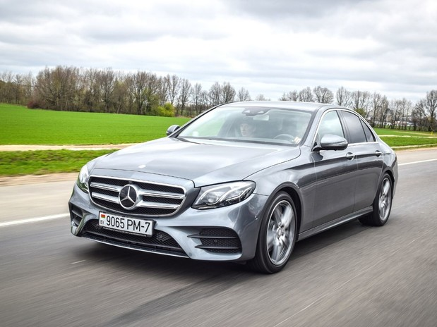 A grey Mercedes E-class driving on a quiet road in front of a field with trees