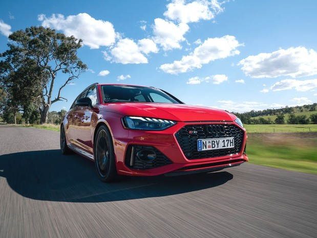Audi RS4 driving on an empty road, in front of a sunny field with trees
