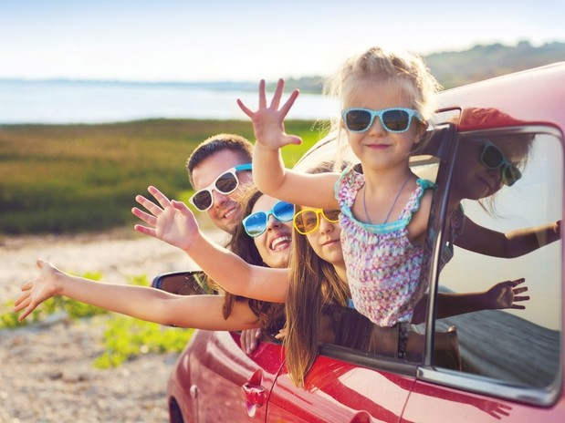 A family of four smiling and waving out of the front and back window of a red car, set in front of a sunny coast