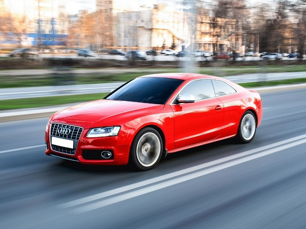 A red Audi A5 driving along a city road.
