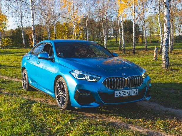 A blue, 2020 BMW 2 Series in a Russian woods during the evening