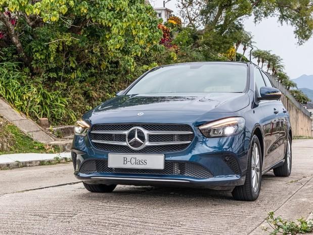 A dark blue Mercedes B-Class in a tropical environment, on a concrete road