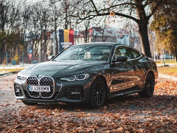 A dark grey 2020 BMW 4 Series on a autumnal road