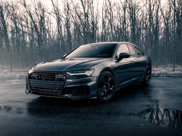 A dark grey 2021 Audi A6 in front of a wintery woodland