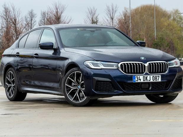 A dark blue 2021 BMW 5 Series in a car park in a wintery setting