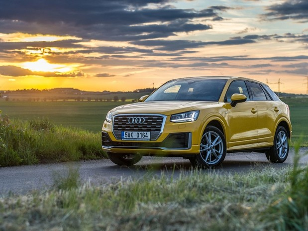A yellow Audi Q2 driving at sunset in front of some fields