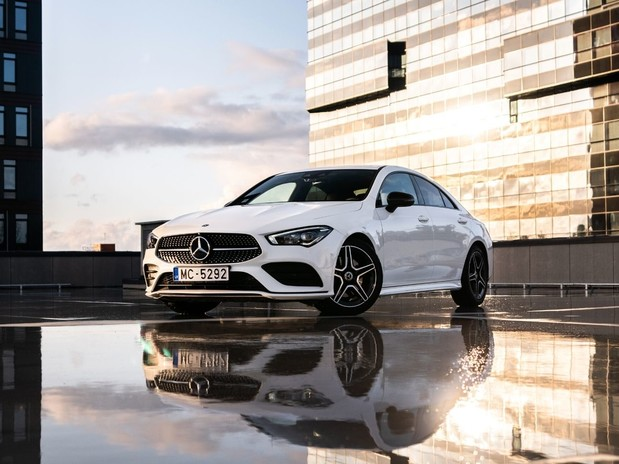 A white, 2019 Mercedes CLA on top of a roof building in the sunset with water reflecting beneath it