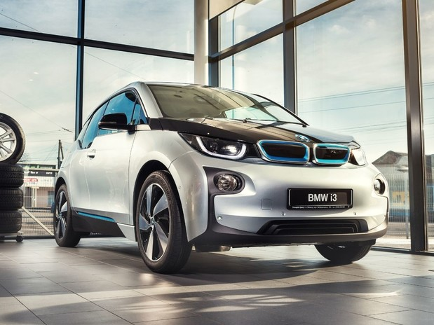 A silver BMW I3 in a showroom, front three quarter view