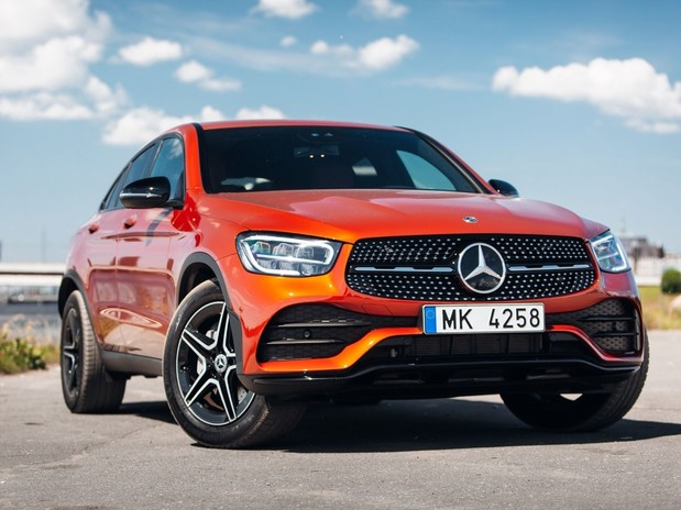 The Mercedes GLA in orange in front of an industrial site