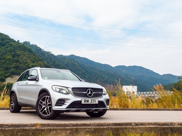 A white Mercedes GLC front three quarter view in front of mountains