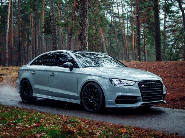 A grey/silver Audi S3 driving through an autumnal forest