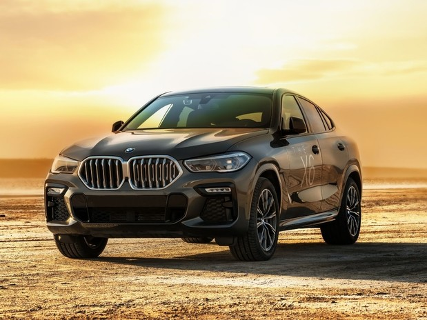 A grey BMW X6 on a lake at sunset