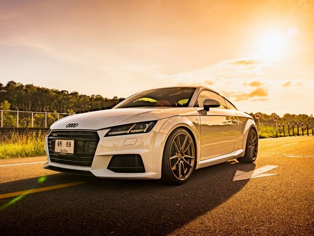 A white Audi TT on a road at sunset